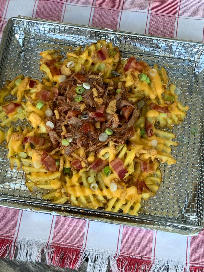 Toaster oven pan of pulled pork, nacho cheese, bacon and onion loaded waffle fries
