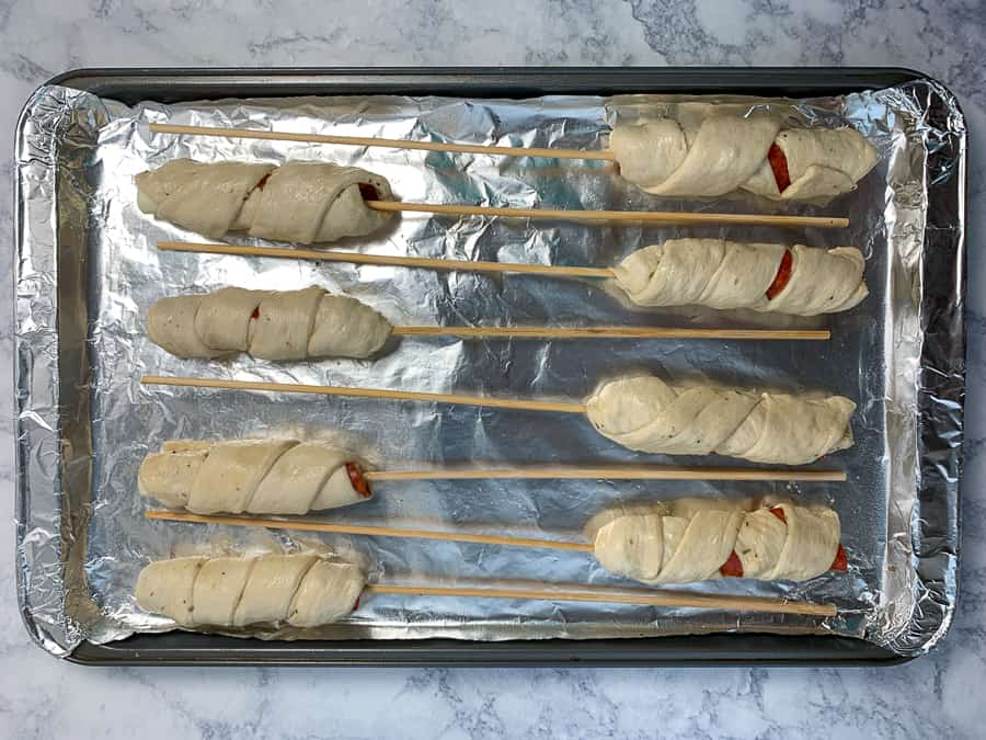 Strips of pizza dough wrapped up around cheese sticks and pepperoni on a baking sheet