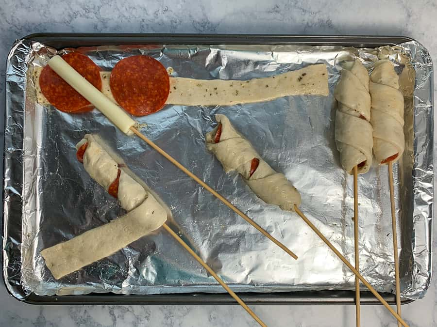 Showing how to wrap pizza dough around pizza on a stick