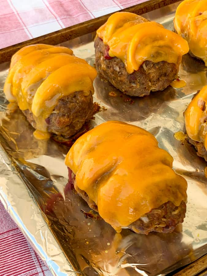 Bacon cheeseburger mini meatloaves on foil covered baking sheet