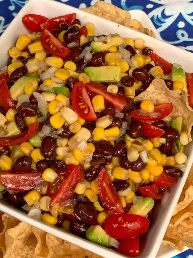 Cold party dip made of black beans, corn, tomatoes, avocado and onions in dish by tortilla chips