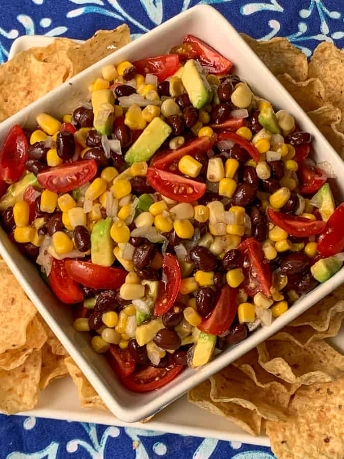 Black bean and corn salsa in white bowl on plate with tortilla chip scoops