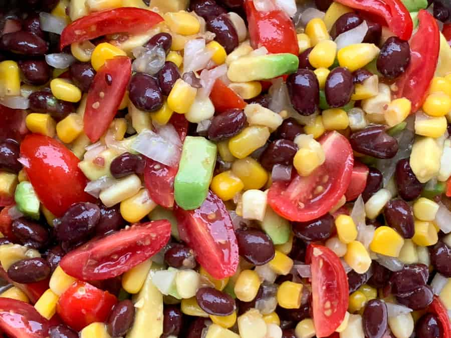 Close up on black beans, corn, avocado, tomatoes, onions and red wine vinaigrette dressing