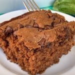 Easy and moist chocolate zucchini cake with chocolate chips on plate with fork