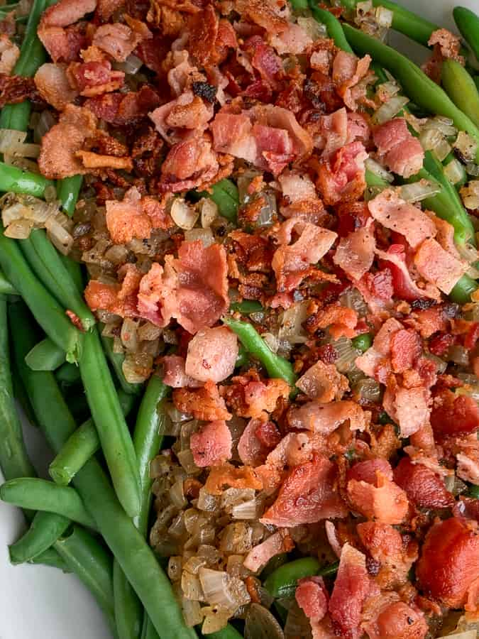 Chopped bacon and sautéed onion covering fresh green bean side dish