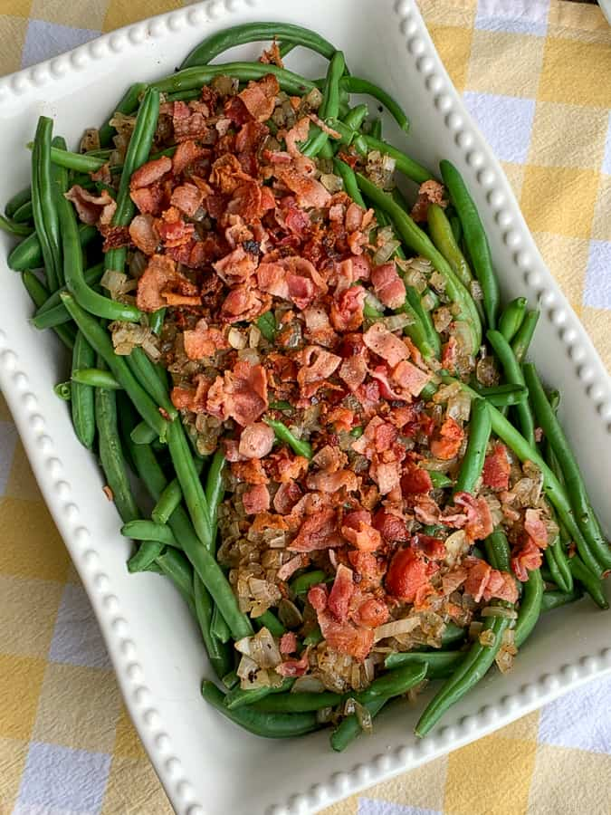 Classic recipe for making fresh green beans; covered with bacon bits and diced onion