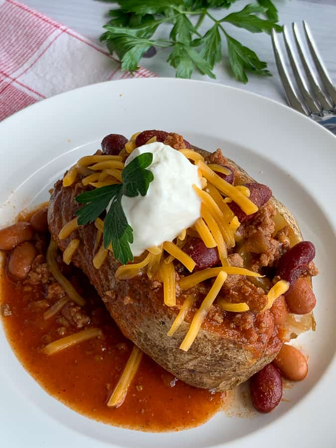 Farmhouse crock pot chili over baked potato with cheese and sour cream on white plate