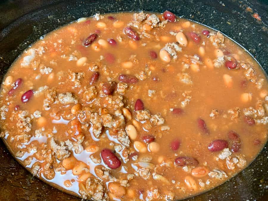 Tomato sauce and tomato paste stirred into crock of chili