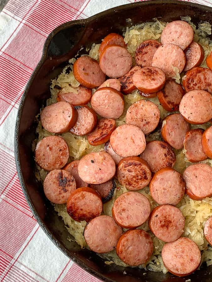 Cast iron skillet with sausage and sauerkraut on red plaid napkin