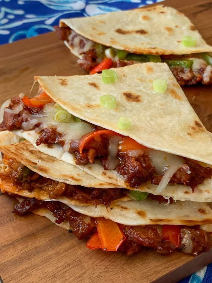 BBQ carnita meat in quesadillas on wood slab on blue napkin