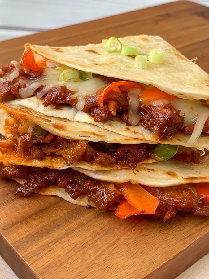Cheese and veggies on BBQ pulled pork quesadillas on wood board