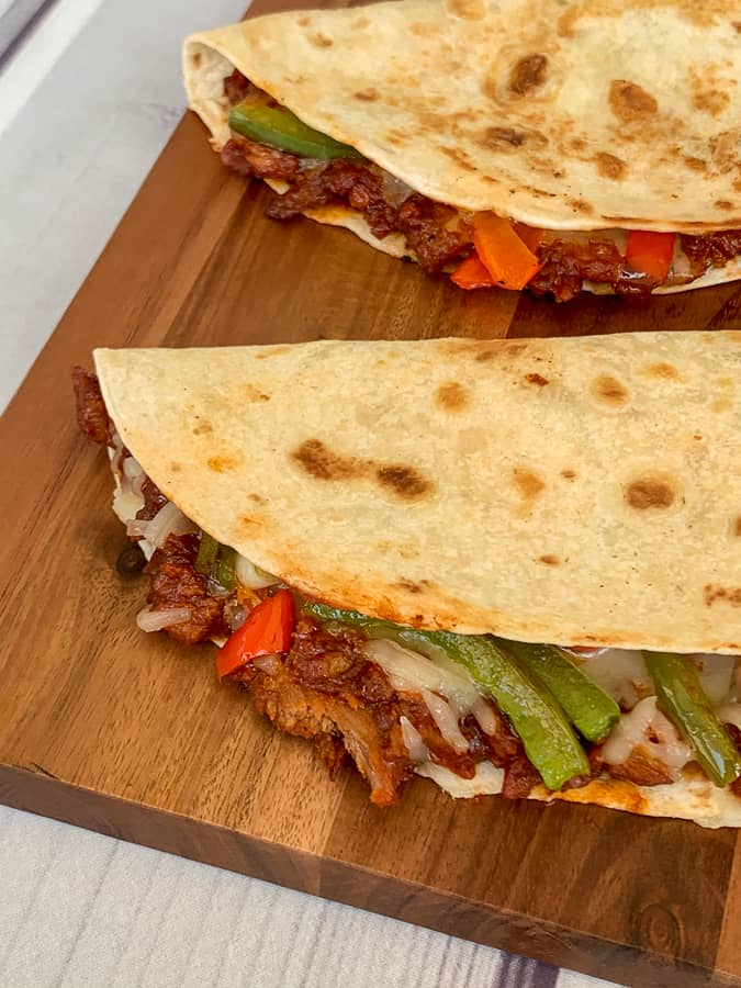 Pulled pork quesadillas with veggies on cutting board and white table