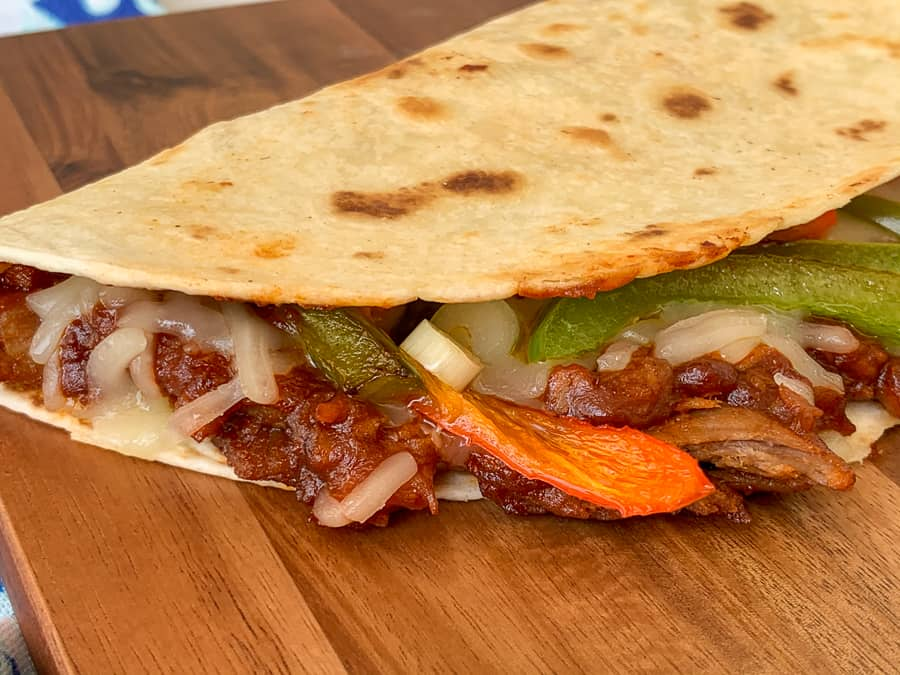 Warm bbq pork quesadilla on cutting board with peppers, green onions and Monterey Jack cheese