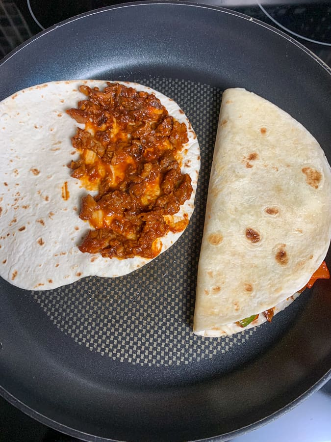 Making bbq pulled pork quesadillas in a skillet