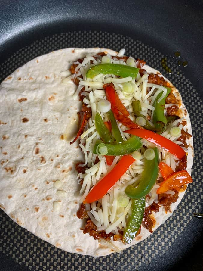 Peppers and onions on bbq pork quesadilla in skillet