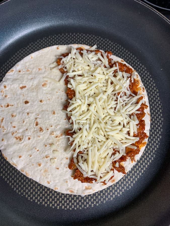 Monterey Jack cheese spread on bbq pork for quesadilla in skillet