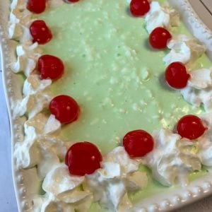 Green jello salad with 7up, whipped cream and cherries