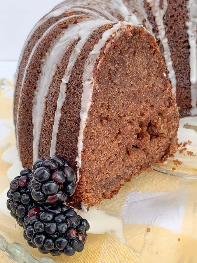 Slice of blackberry bundt cake by fresh berries