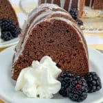 Piece of blackberry jam cake with whipped cream and fresh blackberries