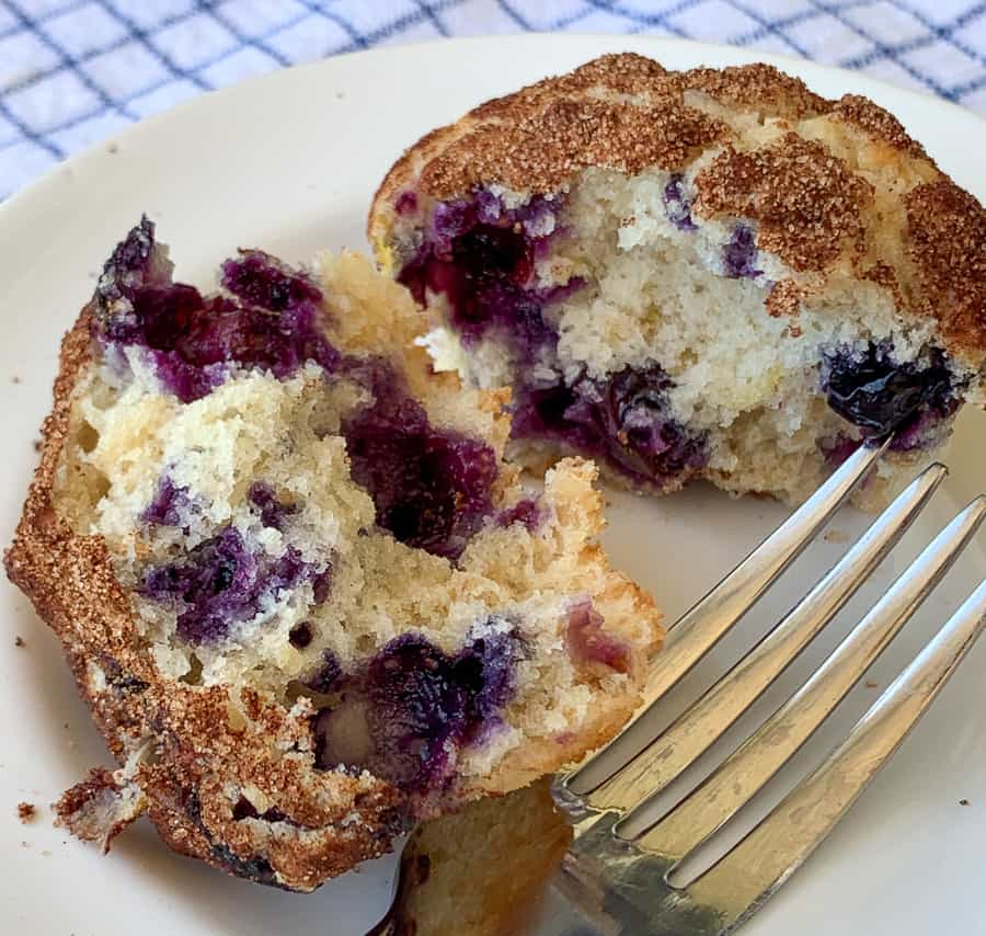 Muffin broken in half revealing blueberries on white plate with fork