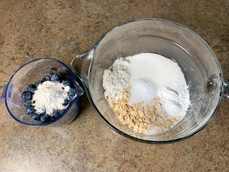 Blueberries and flour in a cup and flour, sugar, oatmeal, salt and baking powder in mixing bowl