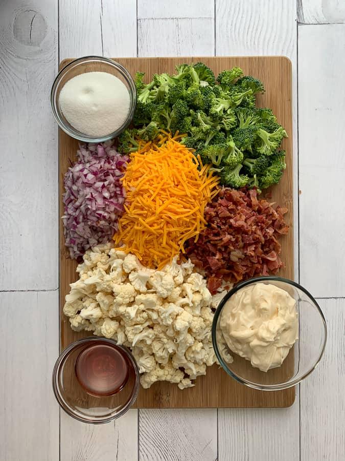 Chopped broccoli, cauliflower, red onion, shredded cheddar cheese, bacon, miracle whip, red vinegar and sugar on cutting board