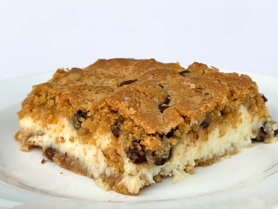 Square chocolate chip cheesecake bar on white plate