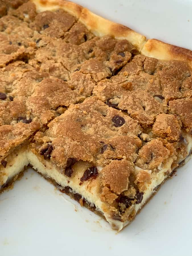 Refrigerator cookie dough rolled out in baking pan to make chocolate chip cheesecake bars