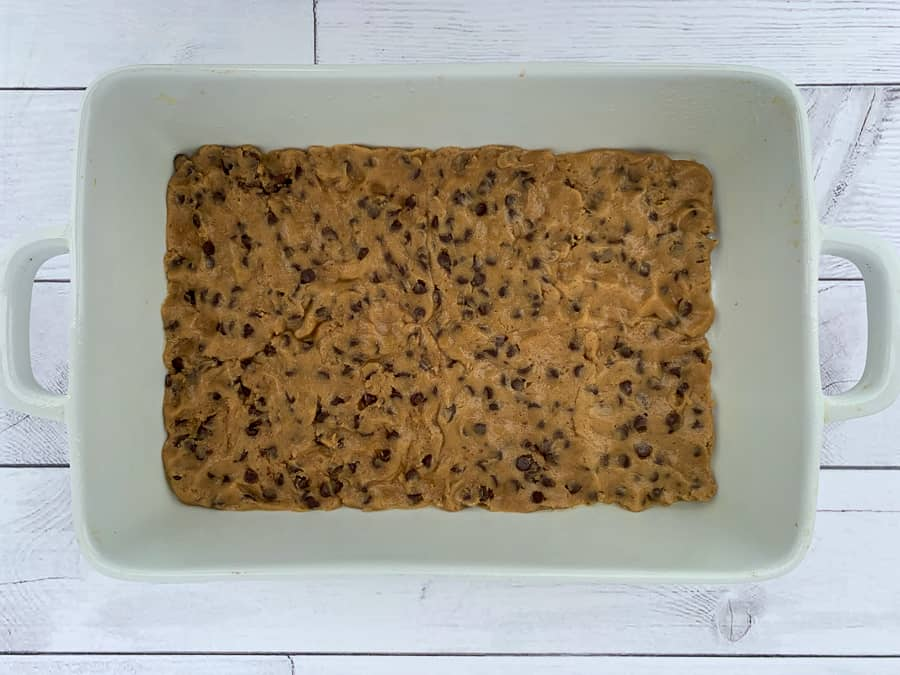 Thin layer of refrigerator chocolate chip cookie dough in 9 x 13 baking pan