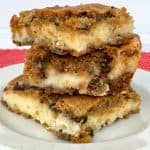 Stack of chocolate chip cookie cheesecake bars on white plate with red napkin