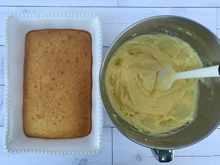 Baked Jiffy Cake Mix in 9x13 dish next to mixing bowl of cream cheese and pudding