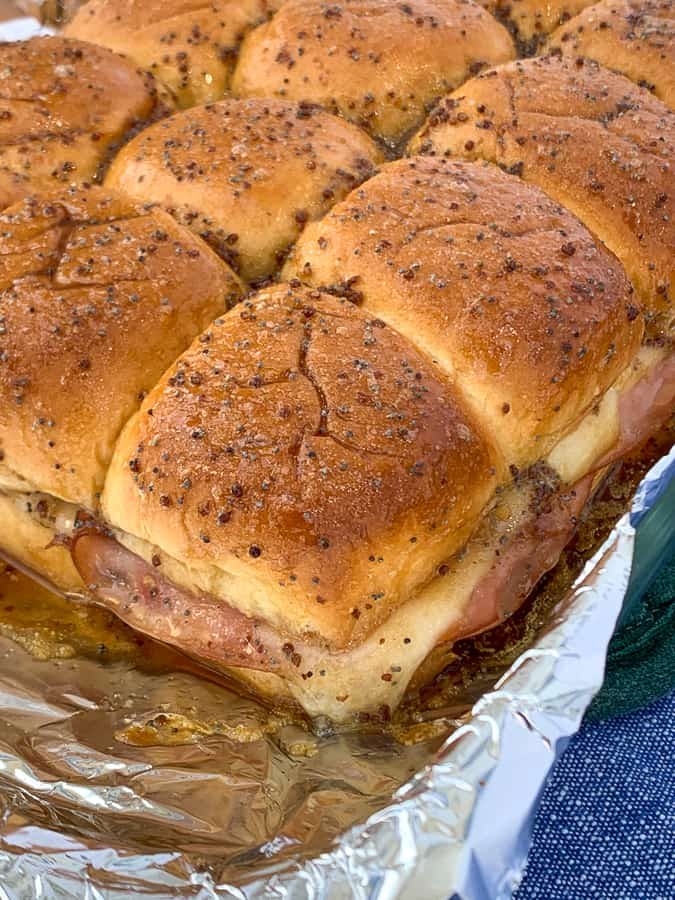 Baked ham and cheese sliders with sweet glaze in foil lined pan