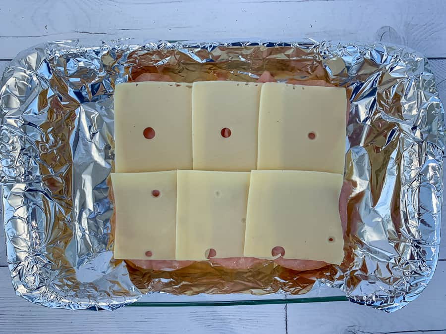 Layer of Swiss cheese added to ham sliders