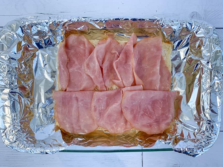 Slices of ham lunch meat on slider rolls