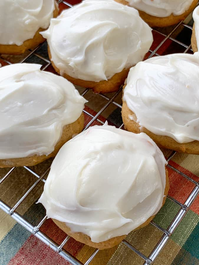 Cream cheese frosting on cookies with pumpkin on a cooking rack