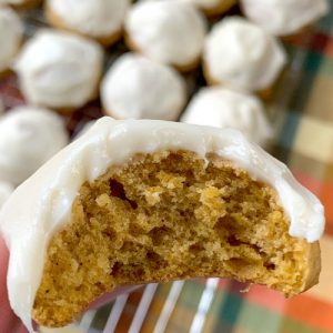 Bite out of moist pumpkin cookie with cream cheese icing