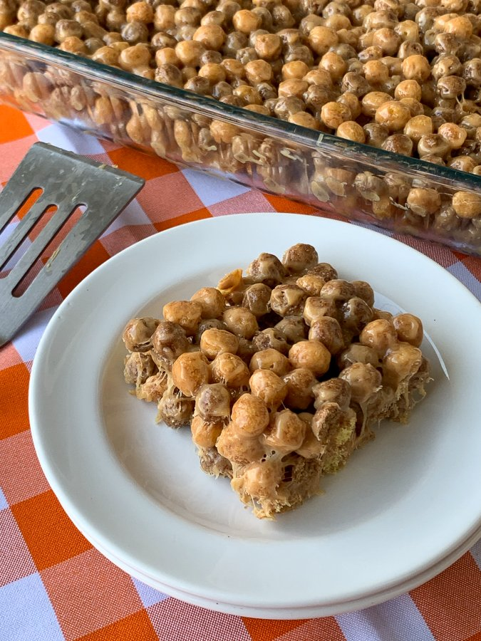 Cereal bar treat made of reese's puffs cereal on white plate by serving spatula