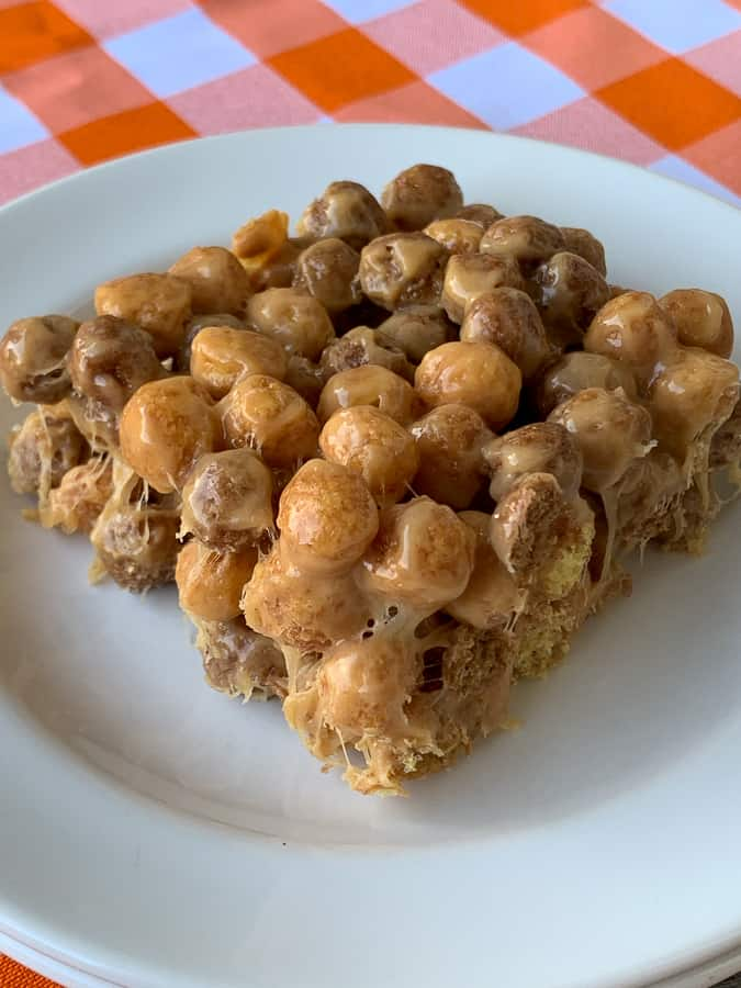 Chocolate and peanut butter puffs treat on white plate and orange plaid napkin