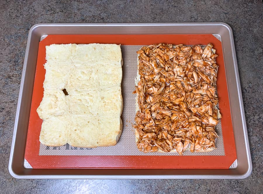 Layer of BBQ shredded chicken on sweet Hawaiian slider rolls