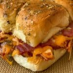 Shredded chicken slider on sweet roll with cheddar, bacon and ranch