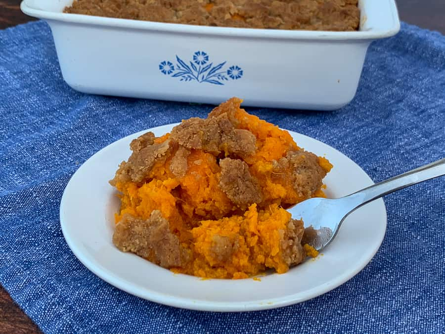 Plate of sweet potato souffle in front of baking dish