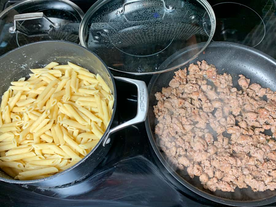 Cooked penne pasta on stove next to browned Italian sausage in a skillet