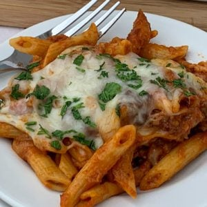 Baked mostaccioli casserole covered in cheese on white plate