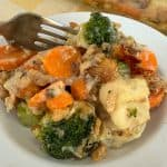 Plate full of baked vegetable medley casserole with a fork
