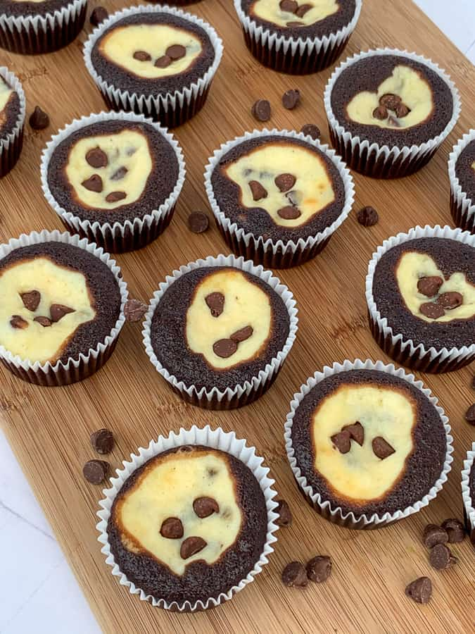 Several homemade chocolate cupcakes filled with cream cheese on a cutting board with extra chocolate chips