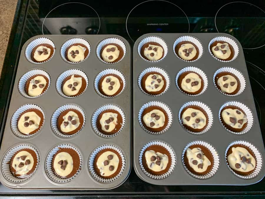 Lined muffin tins filled with batter and chocolate cream cheese to make cupcakes