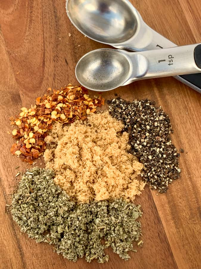 Brown sugar, pepper, red pepper flakes and sage on board with measuring spoons to make homemade sausage