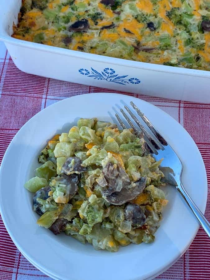 Casserole dish full next to plate with broccoli and mushroom casserole