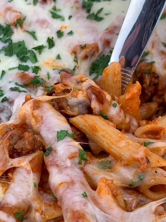 Serving spoon dipped into classic baked mostaccioli