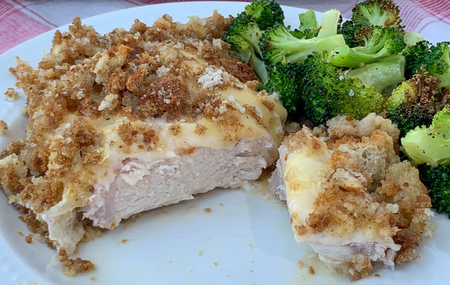 Tender pork loin chop cut in half covered with cheese, creamy mixture and stuffing